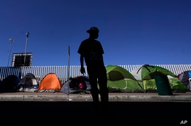 A migrant from Honduras seeking asylum in the United States stands in front of rows of tents at the border crossing, Monday,…