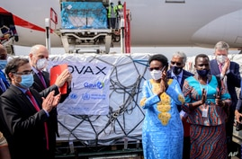 Uganda's Minister of Health Dr. Jane Ruth Aceng, center right, and other officials greet the country's first consignment of…