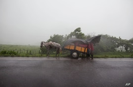 People take cover under a plastic tarp during heavy rain after the San Cristobal volcano spewed smoke and ash, near Chinandega,…