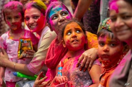 Indians smeared in color participate in Holi festival celebrations in Gauhati, India, Monday, March 29, 2021. Hindus threw…