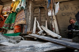 A street vendor waits for customers next to a damaged main door of a Hindu temple, that was vandalized by a group of assailants…