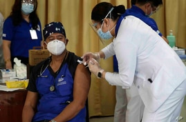 A health worker injects China's Sinovac vaccine on a colleague during the first batch of vaccination at the Lung Center of the…
