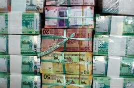 FILE - In this July 24, 2011, file photo, Sudan's new currency sits behind a window at the central bank in Khartoum, Sudan. The…