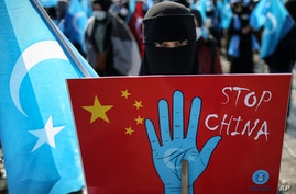A protester from the Uyghur community living in Turkey holds up an anti-China placard during a protest against the visit of…