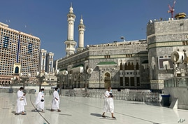 Muslim pilgrims walk outside the Grand Mosque, during the minor pilgrimage, known as Umrah, marking the holy month of Ramadan,…