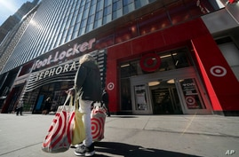 A woman carries Target shopping bags as she leaves the store, Monday, April 19, 2021 in New York. (AP Photo/Mark Lennihan)