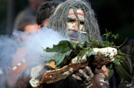 An Aboriginal man performs a smoking ceremony as protesters gather in Sydney, Saturday, June 6, 2020, to support the movement…
