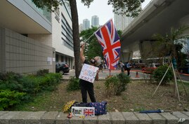 A pro-democracy supporter waves a British flag outside a court in Hong Kong Friday, April 16, 2021. Seven of Hong Kong's…