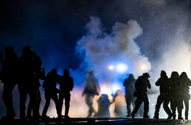 Authorities fire gas munitions at demonstrators gathered outside the Brooklyn Center Police Department to protest the shooting…