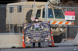 A protester holds his sign in front of the fortified fence and National Guard vehicle protecting the Hennepin County Government…