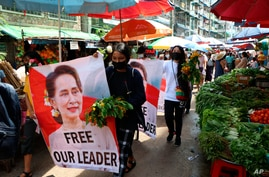 Anti-coup protesters walk through a market with images of ousted Myanmar leader Aung San Suu Kyi at Kamayut township in Yangon,…
