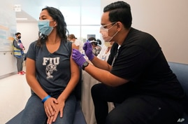 A Florida International University student receives the Pfizer COVID-19 vaccine, April 15, 2021, in Miami.