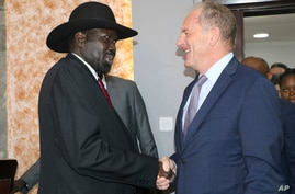 South Sudan's President Salva Kiir, left, shakes hands with U.N. chief, David Shearer, right, during meetings with the U.N…