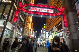 People walk by a street filled with entertainment, restaurants and bars in the Shinjuku neighborhood of Tokyo on Friday, April…