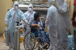 Health workers attend to a patient at the Jumbo COVID-19 hospital in Mumbai, India, Thursday, April 22, 2021. New infections…