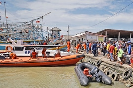Residents look on as members of National Search and Rescue Agency (BASARNAS) prepare for a search mission for the victims of a…
