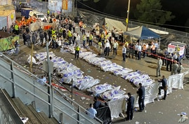 Israeli security officials and rescuers stand around the bodies of victims who died during Lag BaOmer celebrations at Mt. Meron…