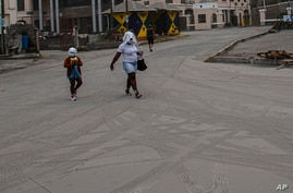 A woman and a girl walk wearing protective head coverings walk on a street covered with volcanic ash a day after the La…