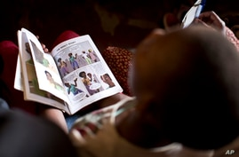 """In this photo taken Monday, Feb. 16, 2015, a child holds a book while attending an HIV prevention session entitled """"Healthy…"""