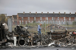A man walks past a burnt out bus on the Shankill road in West Belfast, Northern Ireland, Thursday, April 8, 2021. The scene…