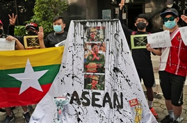 Activists display posters and defaced portraits of Myanmar's Commander-in-Chief Senior General Min Aung Hlaing during a rally…
