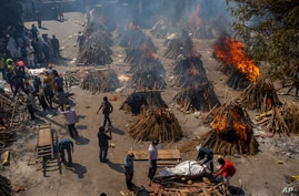 Multiple funeral pyres of victims of COVID-19 burn at a ground that has been converted into a crematorium for mass cremation in…