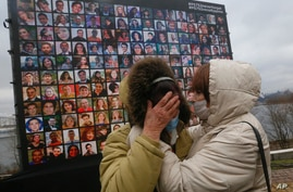 Relatives react at a memorial in Kyiv, Ukraine, Friday, Jan. 8, 2021, for the victims of a Ukrainian 737-800 plane crash on the…