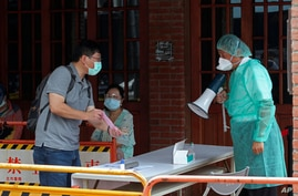 Medical personnel wearing protective gear, guide people at a rapid coronavirus testing center after the infection alert rose to…