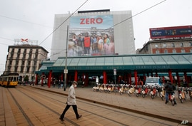 """A man walks under a poster advertising the TV Series """"Zero"""", at Cadorna square in Milan, Italy, Tuesday, April 27, 2021. The…"""