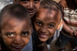 Children displaced by the conflict look into the camera at the elementary school where they now live with their families in the…