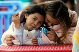 A woman and child embrace under a blanket on the pier, Thursday, May 13, 2021, in Santa Monica, Calif. Counties in California…
