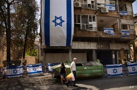 People walk by a residential building covers with Israeli flags after last week it was hit by a rocket fired from the Gaza…