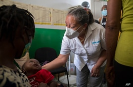 Jean Gough, UNICEF regional director for Latin America and the Caribbean, greets an infant in a malnutrition clinic in Les…