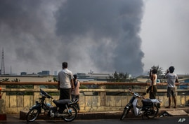 Black smoke billows from the industrial zone of Hlaing Thar Yar township in Yangon, Myanmar Sunday, March 14, 2021. Attacks on…