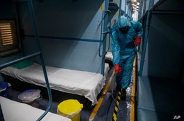 A health worker in personal protective equipment sanitizes a compartment of a train prepared as COVID-19 care centre in the…