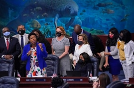 Florida Rep. Tracie Davis, left foreground, is surrounded by supporters as she speaks during a legislative session, Wednesday,…