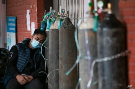 A COVID-19 patient receives oxygen outside an emergency ward at a government-run hospital in Kathmandu, Nepal, Thursday, May 13…