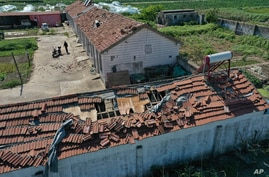 In this photo released by China's Xinhua News Agency, a man stands near damaged buildings and farm fields after a devastating…