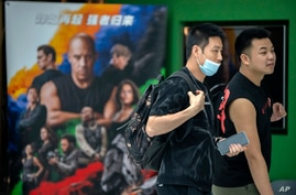 """People walk past a poster for the movie """"Fast & Furious 9"""" at a shopping mall in Beijing, Wednesday, May 26, 2021. Pro…"""