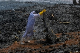 A Sri Lankan navy soldier hauls debris washed ashore from the burning Singaporean ship MV X-Press Pearl which is anchored off…