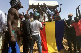 Mourners chanting as some hold the coffin during the funeral of one of the victims who was killed earlier this week, at a…