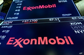 The logo for ExxonMobil appears above a trading post on the floor of the New York Stock Exchange, Tuesday, Oct. 8, 2019. (AP…