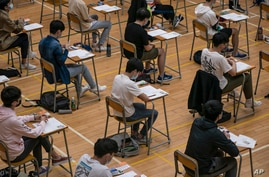 Students sit for the Diploma of Secondary Education (DSE) exams Monday, April 26, 2021 in Hong Kong. Temperature checks and…