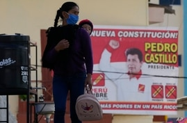 CORRECTS NAME OF LOCATION - A woman carries her child on her back past an electoral poster promoting Free Peru party…