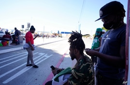 Jean Adler Cactus, right, a Haitian migrant seeking asylum in the United States, works on the hair of Haitian migrant Thomas…