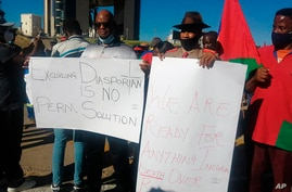 People hold banners as they stage a protest in Windhoek, Namibia, Friday May 28, 2021. Germany has reached an agreement with…
