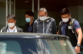 Police officers escort Cheung Kim-hung, right, CEO and Executive Director of Next Digital Ltd at Apple Daily headquarters in…