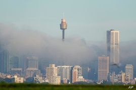 Fog drifts through the buildings in Sydney's central business district, Australia, Friday, June 11, 2021. The fog on Sydney…