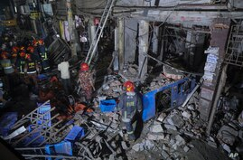 Rescuers stand amid the debris after a blast at a market in Dhaka, Bangladesh, Sunday, June 27, 2021. (AP Photo)