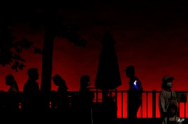 A policemen is silhouetted as he stands watch visitors walk near Tiananmen Gate on the eve of the June 4 anniversary in Beijing…